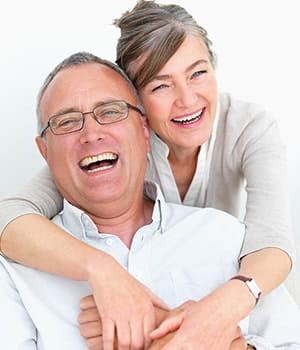 Older couple laughing after receiving periodontics treatment at our dentist office in Midtown Manhattan
