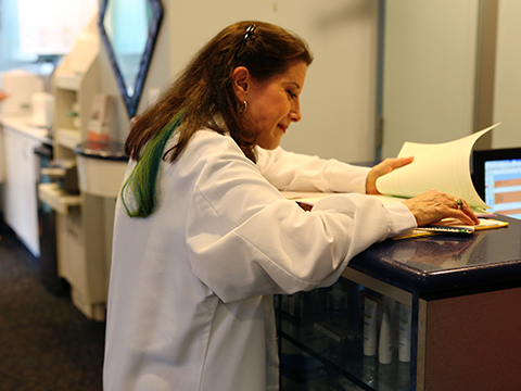 Image of our dentist in New York, Dr. Kantor-Goldenberg doing paperwork