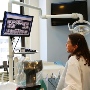 Midtown Cosmetic Dentists - Image showing dentist using modern technology to care for her patients.