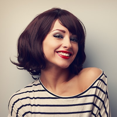Attractive woman with short brown hair, red lipstick and a striped shirt, smiling at the camera because her smile was enhanced with porcelain veneers which is offered as part of our cosmetic dentistry in NYC