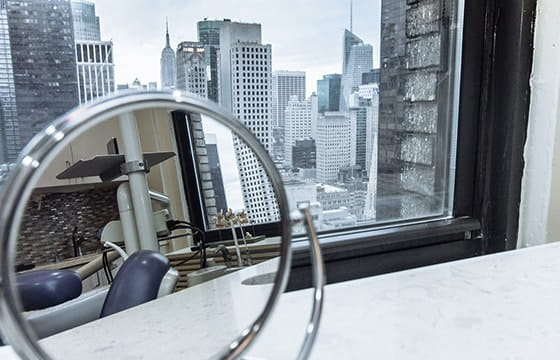 Window view of New York with a mirror view of the dental chair