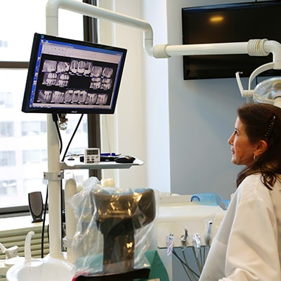 A dentist looking at xrays in preparation for All-on-four dental implants in Lennox Hill New York