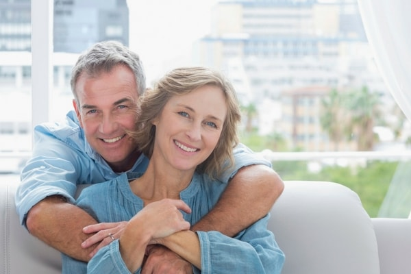 Mobile and tablet image of couple enjoying their smiles after teeth whitening