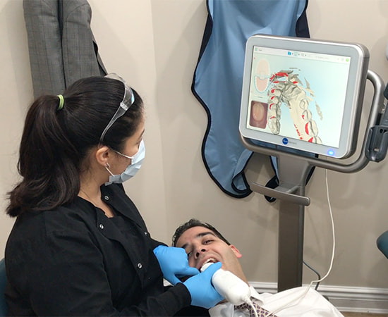 One of our Midtown Dental Excellence employees using the iTero scanner, which is part of our dental technology