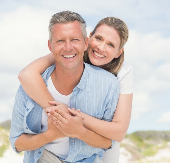 A smiling couple who are free from tooth pain after root canal therapy