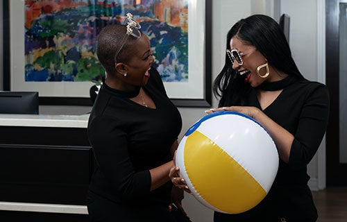 Part of the team at Midtown Dental Excellence laughing and holding a beach ball